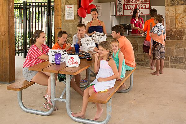 Children outdoors at Woodforest's Forest Island enjoying fast food